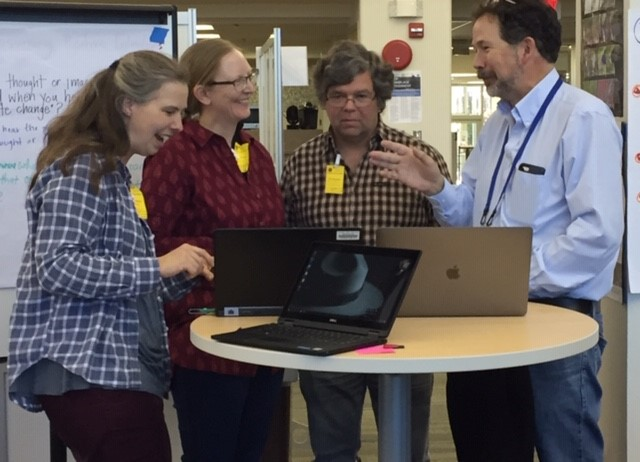Two women and two men smiling and sharing excitement about NASA visuals on a laptop